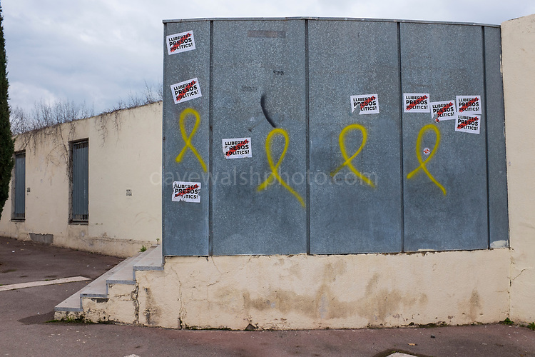 Pro-Catalan independence graffiti and stickers, on the wall of the Biblioteca Central Gabriel Ferrater (municipal library) Sant Cugat del Valles, Barcelona, Catalonia.<br /> &ldquo;Llibertat Presos Politics&rdquo; is Catalan for &ldquo;free political prisoners&rdquo;, while the yellow ribbon signifies solidarity with the politicians and civic leaders who were held, or are being held in Spanish prisons.  One resident of Sant Cugat, Catalan Foreign Minister Raul Romeva, was amongst those jailed.