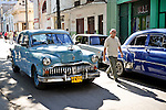 HAVANA - DECEMBER 30: A vintage car driving down a street in Havana, Cuba.  Legislation passed in 2011 has legalized car sales to all Cuban citizens who were previously restricted to owning pre-revolution vehicles.