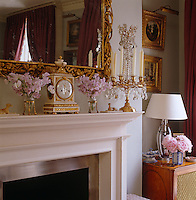 A detail of the mantelpiece in the drawing room accessorised with a gilt candelabra, ormolu carriage clock and a gilt-framed mirror