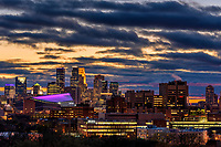 Sunset over downtown Minneapolis with the roof of USBank Stadium lit purple.