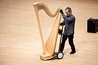 Lyon and Healy Technician John Papadolias moves a harp between performances during Stage III at the 11th USA International Harp Competition at Indiana University in Bloomington, Indiana on Wednesday, July 10, 2019. (Photo by James Brosher)