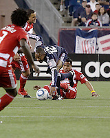 New England Revolution defender Cory Gibbs (12) is tackled from the ground by FC Dallas forward David Ferreira(10).  The New England Revolution drew FC Dallas 1-1, at Gillette Stadium on May 1, 2010
