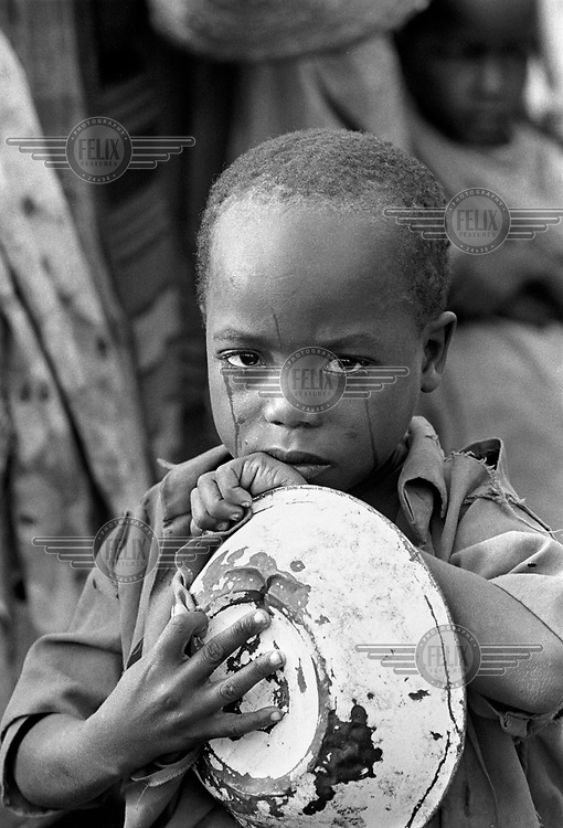 © Paul Lowe / Panos Pictures..Baidoa, SOMALIA  1992.A child cries whilst waiting for food at a feeding centre during the 1992 famine caused by the civil war in Somalia..In 1991 President Barre was overthrown by opposing clans,  but they failed to agree on a replacement and plunged the country into lawlessness and clan warfare. In December 1992 US Marines landed  near Mogadishu ahead of a UN peacekeeping force sent to restore order and safeguard relief supplies.  The US forces withdrew in 1993 following the debacle of Black Hawk Down..CROPPED OR DIGITALLY MODIFIED IN ANY MEDIUM AND ITS CAPTION MAY NOT BE ALTERED WITHOUT THE PRIOR WRITTEN AUTHORISATION OF THE PHOTOGRAPHER OR HIS AGENT...