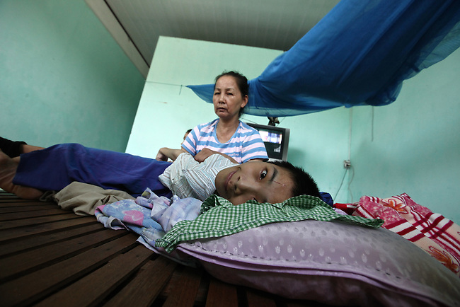 "Le Thi Phung cares for her 19-year-old son, Mai Dinh Tu, a second generation victim of Agent Orange, in their house south of Da Nang, Vietnam. Phung's husband served as a bomb disposal soldier from 1975 to 1990 and worked in many areas that had been sprayed with herbicides sprayed during the war. ""He had to go to many dangerous places,"" says retired Col. Thai Thanh Hung, chairman of the Da Nang Veterans Association. ""He could not refuse the orders."" Phung's first child was born mentally disabled, and her son Tu was born with disorders that have left him  unable to talk or even sit up on his own. The Vietnam Red Cross estimates that 3 million Vietnamese suffer from illnesses related to dioxin exposure, including at least 150,000 people born with severe birth defects since the end of the war. The U.S. government is paying to clean up dioxin-contaminated soil at the Da Nang airport, which served as a major U.S. base during the conflict. But the U.S. government still denies that dioxin is to blame for widespread health problems in Vietnam and has never provided any money specifically to help the country's Agent Orange victims. May 30, 2012."