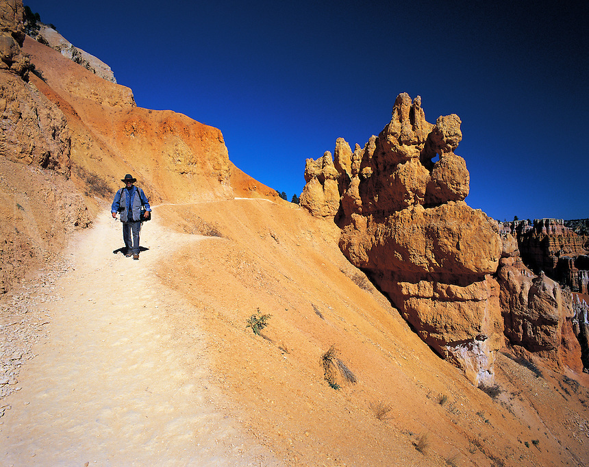 Walker descending footpath past pinnacles and other formations into Bryce Canyon, Utah, US