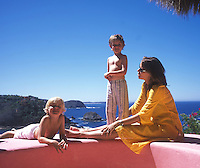 """Alison Chace, New York based host of PLUMTV, with her two sons; Finn 6 and Callum 4, enjoy the view from their house """"Casa Parasol"""" Careyes, Mexico."""