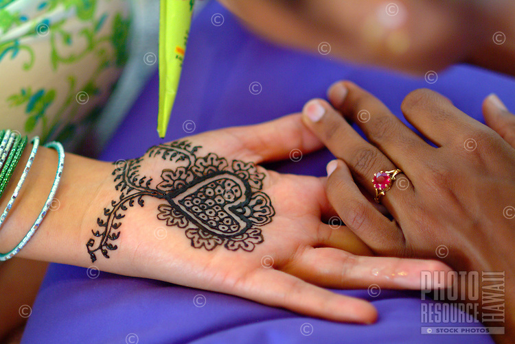 Woman receiving a mendhi henna design on the inside of palm of a her hand in preparation for her hindi wedding ceremony
