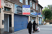 Two women wearing traditional Muslim dress pass empty shop premises to let in Cricklewood, London.