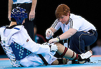 04 DEC 2011 - LONDON, GBR - A medic tends the knee of Sang-Bin Lee (KOR) during his men's -80kg category preliminary round contest against Uriel Adriano-Ruiz (MEX) at the London International Taekwondo Invitational and 2012 Olympic Games test event at the ExCel Exhibition Centre in London, Great Britain .(PHOTO (C) NIGEL FARROW)