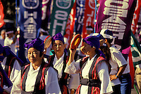 Women with banners marching in annual Okinawan Festival parade.
