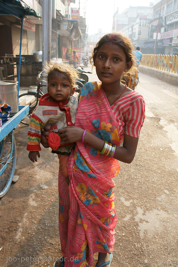 mother and son on the streets of Varanasi. Next to a food place on the streets, this woman was begging for food.