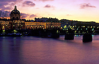 View of the French Institute illuminated at twilight over the Seine, Paris, France.