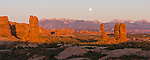 Panorama of a full moonrise over the La Sal Mountains and Balanced Rock in Arches National Park, Moab, Utah, USA at sunset with cloudless skies.