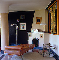 A tan Mies Van der Rohe Barcelona daybed and a 1920s side table stand in front of a fireplace in the corner of a living room