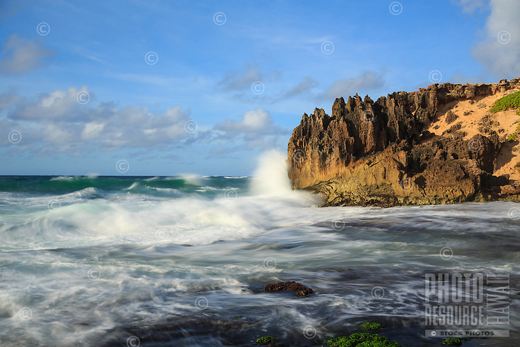 At sunrise, a wave breaks against the pinnacles along Maha'ulepu Heritage Trail on Kaua'i's southern shore.