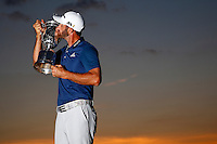 Dustin Johnson kisses the U.S. Open trophy following his first major win in Oakmont, Pennsylvania on Sunday June 19, 2016. (Photo by Jared Wickerham / DKPS)