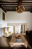 In the main living room the furniture is in a simple rustic style to complement the rough stone walls and exposed oak beams