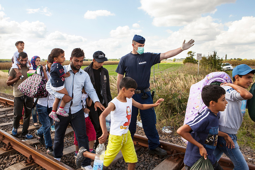 A policeman directs Refugees at Roszke Crossing on Serbian-Hungarian Border to a temporary holding area.