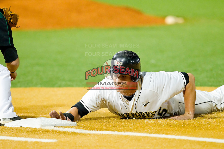 Matt Conway #25 of the Wake Forest Demon Deacons dives back towards first base during the game against the Charlotte 49ers at Gene Hooks Field on March 22, 2011 in Winston-Salem, North Carolina.   Photo by Brian Westerholt / Four Seam Images