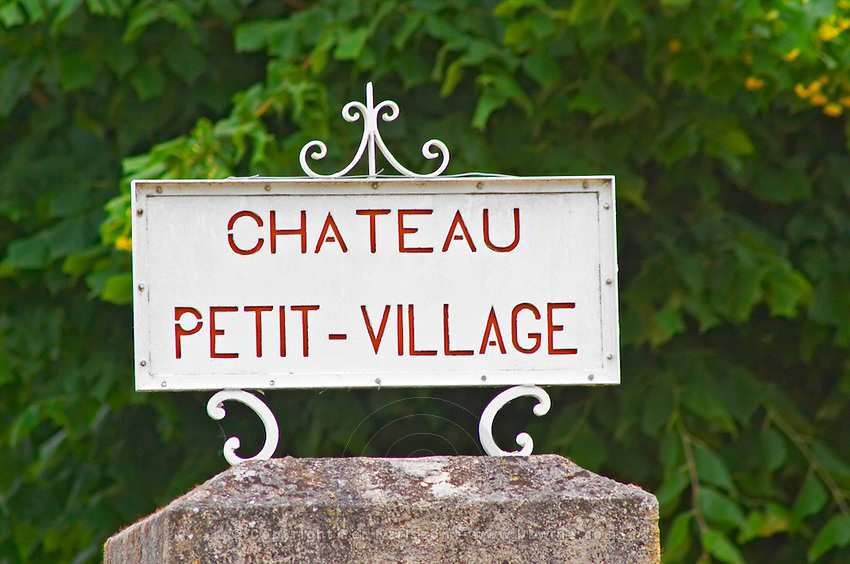 A stone gate post and a white sign saying Chateau Petit Village, detail Pomerol Bordeaux Gironde Aquitaine France
