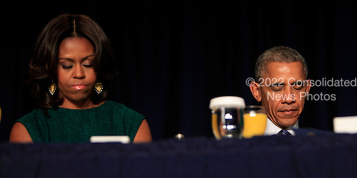 United States President Barack Obama and first lady Michelle Obama bow their heads in prayer at the National Prayer Breakfast  at the Washington Hilton Hotel in Washington, D.C. on February 5, 2015.  U.S. and international leaders from different parties and religions gather annually at this event for an hour devoted to faith and prayer. <br /> Credit: Dennis Brack / Pool via CNP