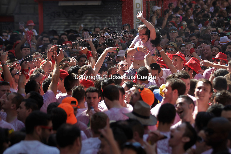 "Revellers tear clothes of a woman, while they throw wine over her in the first day of Sanfermines, in city hall square, in Pamplona, northern of Spain. San Fermin starts with the launch of a rocket, which is known as ""chupinazo"". San Fermin festival is worldwide known because the daily running bulls."