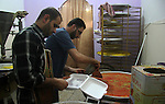 Palestinian former prisoners Hamouda Salah and Radwan Abu Turki, make Kunafa at their sweet store in Gaza city on March 29, 2013. Salah and Abu Turki was released by Israel as part of the Gilad Shalit prisoner exchange agreement and banished from the West Bank city of Hebron to Gaza City. Photo by Ezz al-Zanoon