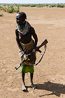ETHIOPIA, Southern Nations, Lower Omo valley, Kangaten, village Kakuta, Nyangatom tribe, woman with machine gun Kalashnikov AK-47 for protection from cattle raids by neighbor Turkana warriors / AETHIOPIEN, Omo Tal, Kangaten, Dorf Kakuta, Nyangatom Hirtenvolk, Frau mit Maschinengewehr Kalaschnikow AK-47 zum Schutz vor Ueberfaellen durch Turkana Krieger