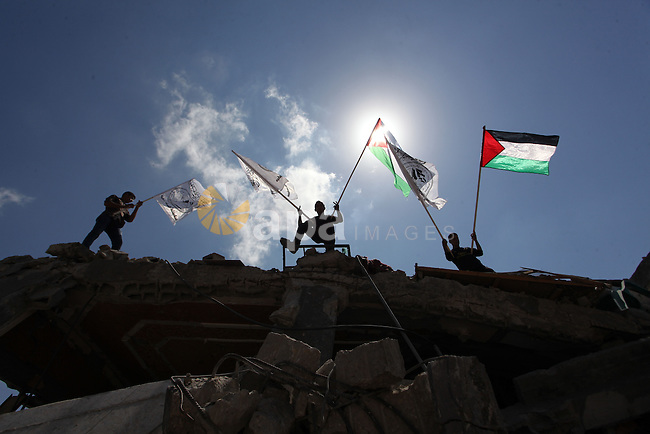 Palestinians hold national flags during a protest in the Shejaia neighbourhood, east of Gaza City. September 6, 2014. Calm returned to the coastal enclave in a August 26 ceasefire, and Gazans were gradually starting to rebuild their lives after a bloody and destructive 50-day war, the deadliest for years. Photo by Ashraf Amra