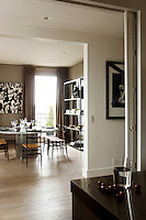 The open-plan apartment is arranged around a central corridor; in this view the kitchen opens out to the dining room