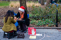 New York, NY 25 December 2015 - A Palm reader predicts a woman's on Christmas Day in Washington Square Park. Temperatures reached into the mid 60s on this unseasonably warm CHristmas.