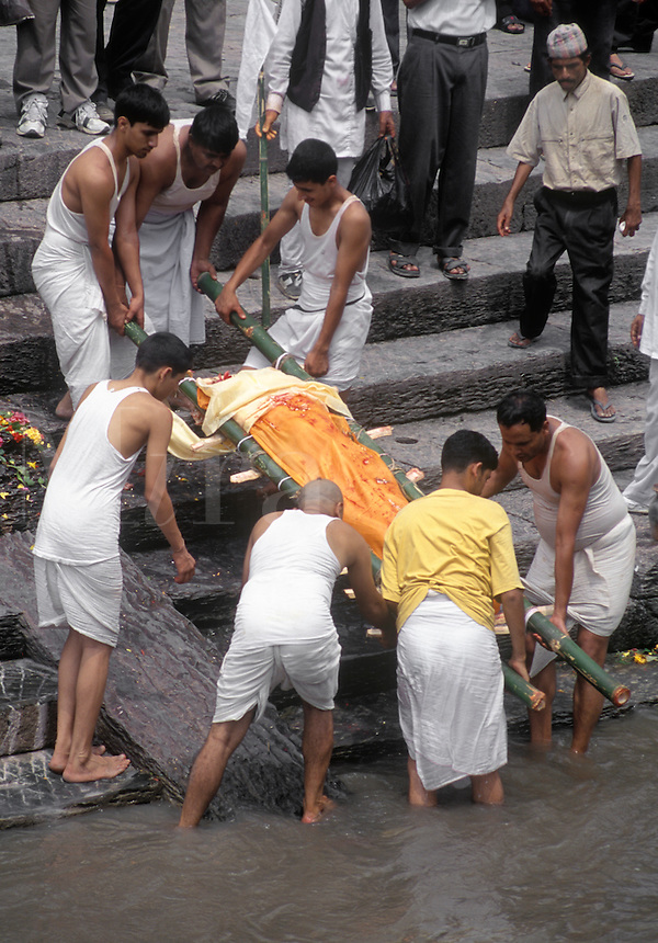Last rights are preformed on a man before CREMATION at the PASHUPATINATH BURNING GHATS - KATHAMANDU, NEPAL