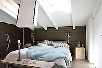 The master bedroom is painted a restful shade of khaki and white with a simple bedside table made from a rough-hewn section of tree trunk