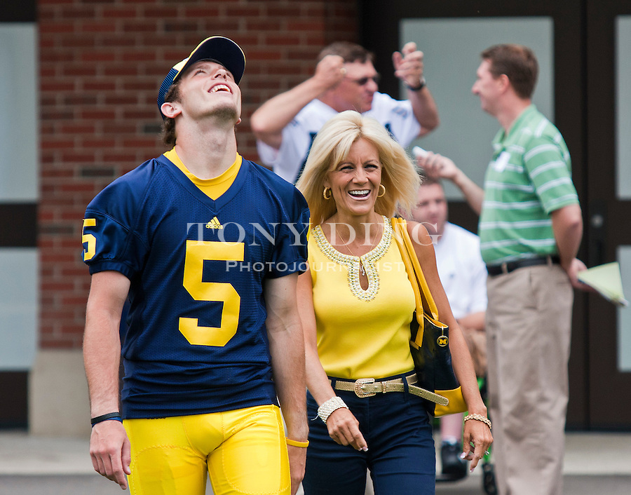 Michigan quarterback Tate Forcier (5) laughs as he walks with head coach Rich Rodriguez's wife Rita, at the annual NCAA college football media day, Sunday, Aug. 22, 2010, in Ann Arbor, Mich. (AP Photo/Tony Ding)