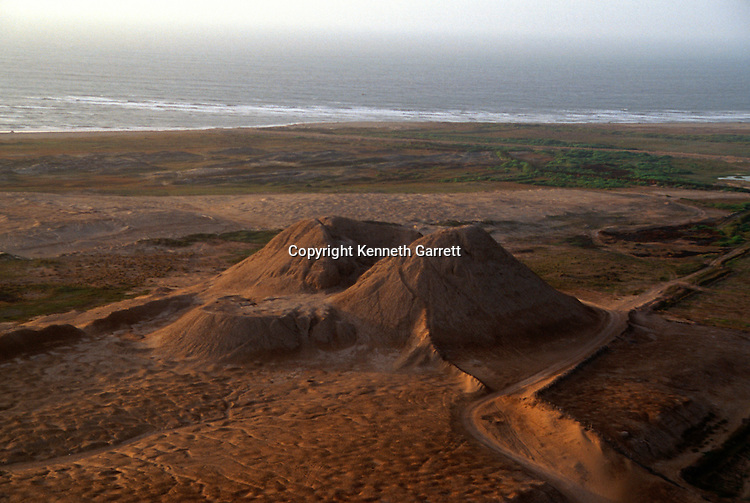 Aerial view of Huaca Dos Cabezas, corner of mudbrick pyramid, was looted by the Spanish, Pacific ocean on the horizon, Jecetepeque, Peru