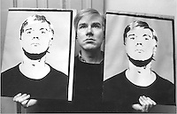 Andy Warhol holding two self portraits.