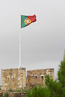 Portuguese flag fluttering on the Castelo de Sao Jorge fortress. Lisbon, Portugal