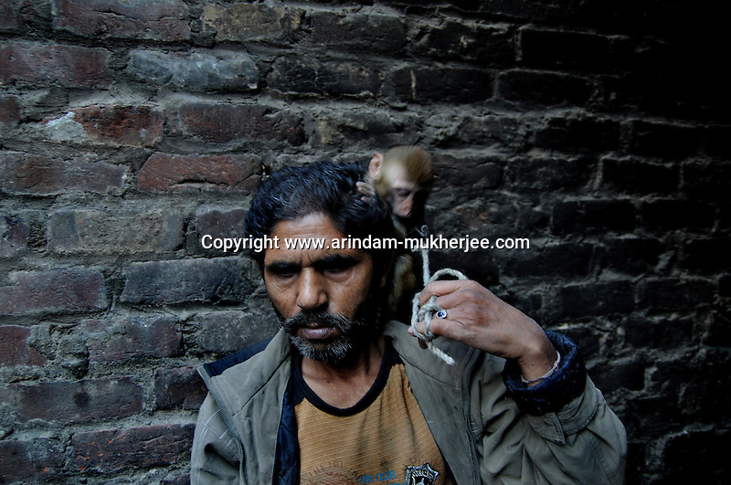 Suresh and his pet monkey at Katputly colony in New Delhi, India. 17.11.2009. Kathputly colony is a slum area in West Delhi. This slum seems like any other slum areas of modern India with dysfunctional electricity, non existing sanitation and poverty. As a part of Delhi, this is also ailed with water crisis. Large families live their lives crammed together in a single room with all the odds which complement poverty. One thing which differentiates this slum with any other is the people living in the colony. Nearly everybody in this slum is a traditional performing artist; and they have been migrating to this area for last 50 years from different parts of the country for a better livelihood. They are magicians, acrobats, jugglers, puppeteers, dancers and musicians. These artistes perform in star rated hotels, marriage ceremonies of the richer section, functions, and festivities all around the country and the world. Most of the artisans I met here, have performed in Europe and America but such opportunities are rare to come by. They struggle to keep their art form alive. They say that they don't get any help or support from the government for their basic needs and for the well being of the Kathputly colony -  though they have uphold the prestige of the country internationally. Polluted air, dirty alleys smelling of urine, colourful dress and sound of music characterise Kathputly colony, which is the one of its kind in India. Arindam Mukherjee