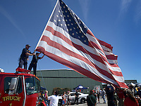 NWA Democrat-Gazette/BEN GOFF @NWABENGOFF<br /> Firefighters lower a large U.S. flag on Saturday Sept. 12, 2015 during the Sheep Dog Impact Assistance annual Patriot Day event at Bentonville Municipal Airport. The event honored the victims of the Sept. 11, 2001 terrorist attacks and offered visitors a chance to get an up close look at military and emergency response vehicles.