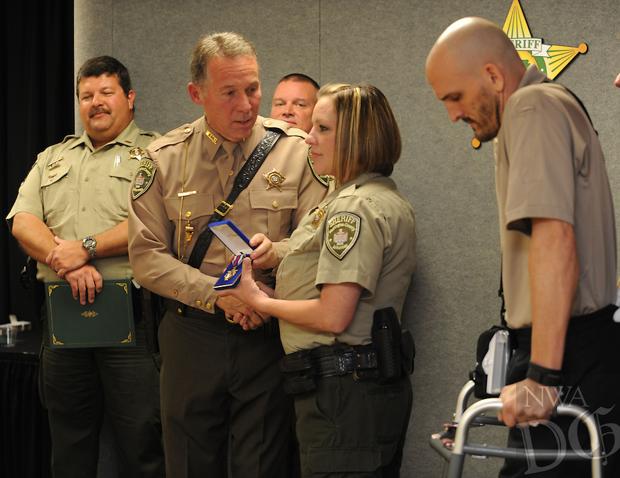 NWA Democrat-Gazette/ANDY SHUPE<br /> Sgt. Oscar Henson (center) reaches to hug Lt. Tion Augustine Thursday, March 31, 2016, after receiving the Washington County Sheriff's Office's Medal of Valor during a ceremony at the sheriff's office annex in Fayetteville. Henson helped to pull Augustine to safety after he was shot while responding to a call March 15 in Fayetteville.