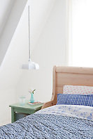 A white enamel lamp, found in a second hand shop, hangs above a green stool which serves very well as a bedside table