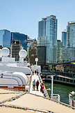 CANADA, Vancouver BC, couples walk around on deck of the Holland America cruise ship, the Oosterdamat, while at port by the Canada Place, British Columbia