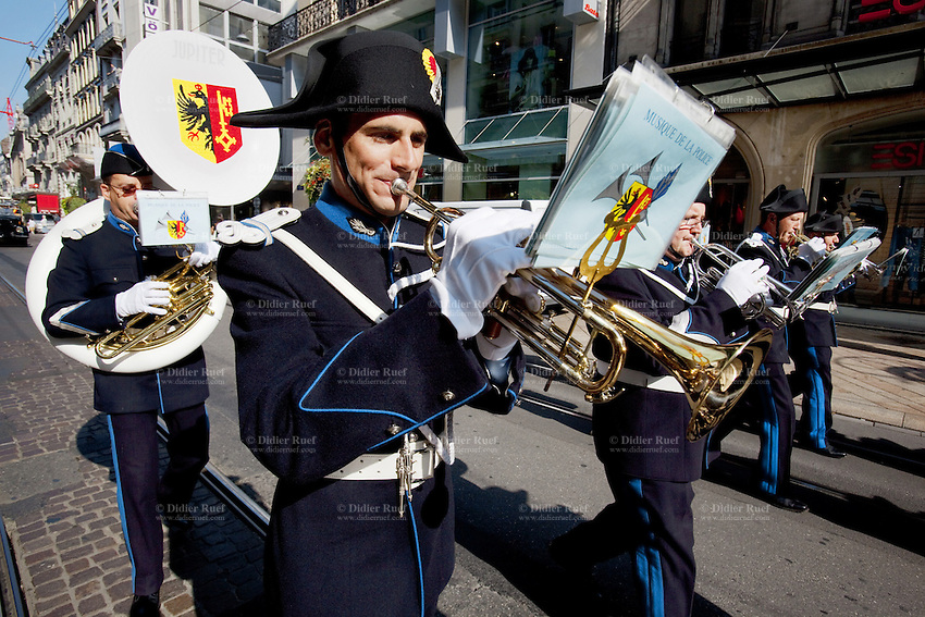 "Switzerland. Geneva. Policemen from police band play music and walk on the day in which young policemen and policewomen from the police academy will be sworn in as police officers. They wear uniforms, white gloves, tricorns on the heads. They play the trumpets and the sousaphone. The trumpet is the musical instrument with the highest register in the brass family. The sousaphone is a type of tuba that is widely employed in marching bands. Designed so that it fits around the body of the musician and is supported by the left shoulder, the sousaphone may be readily played while being carried. The tricorne or tricorn is a style of hat that was popular during the 18th century, falling out of style by 1800. The tricorne was worn as part of military uniforms. The flag of Geneva is divided vertically into two equal parts, yellow (hoist) and red (fly). In the hoist, a black double-eagle with a red crown, beak, tongue, legs and claws, cut in half by the palar line. In the fly, a yellow upright key with its ward toward the fly. The eagle symbolises loftiness, justice and protection. The key symbolises ecclesiastical rule, treasuries, and responsibility. The arms of Geneva are actually two shields impaled: half the eagle of the Holy Roman Empire, and one of the two keys of St. Peter (the ""keys of heaven"". 29.08.12 © 2012 Didier Ruef..."