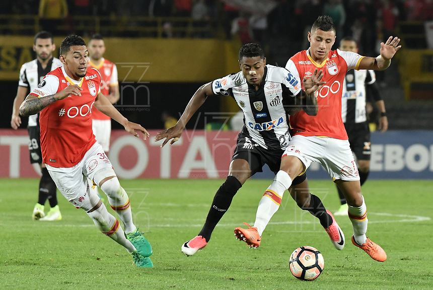 BOGOTÁ-COLOMBIA-19-04-2017: Juan Daniel Roa (Der) y Yeison Gordillo (Izq) de Independiente Santa Fe de Colombia disputan el balón con Bruno Henrique (C) jugador de Santos de Brasil, durante partido por la fecha 3, fase de grupos, de la Copa CONMEBOL Libertadores Bridgestone 2017  jugado en el estadio Nemesio Camacho El Campin de la ciudad de Bogotá. / Juan Daniel Roa (R) and Yeison Gordillo (L) players of Independiente Santa Fe of Colombia fight for the ball with Bruno Henrique (C) player of Santos of Brazil during the match for the date 3, groups phase, of the Copa CONMEBOL Libertadores Bridgestone 2017  played at Nemesio Camacho El Campin stadium in Bogota city.  Photo: VizzorImage/ Gabriel Aponte /Staff