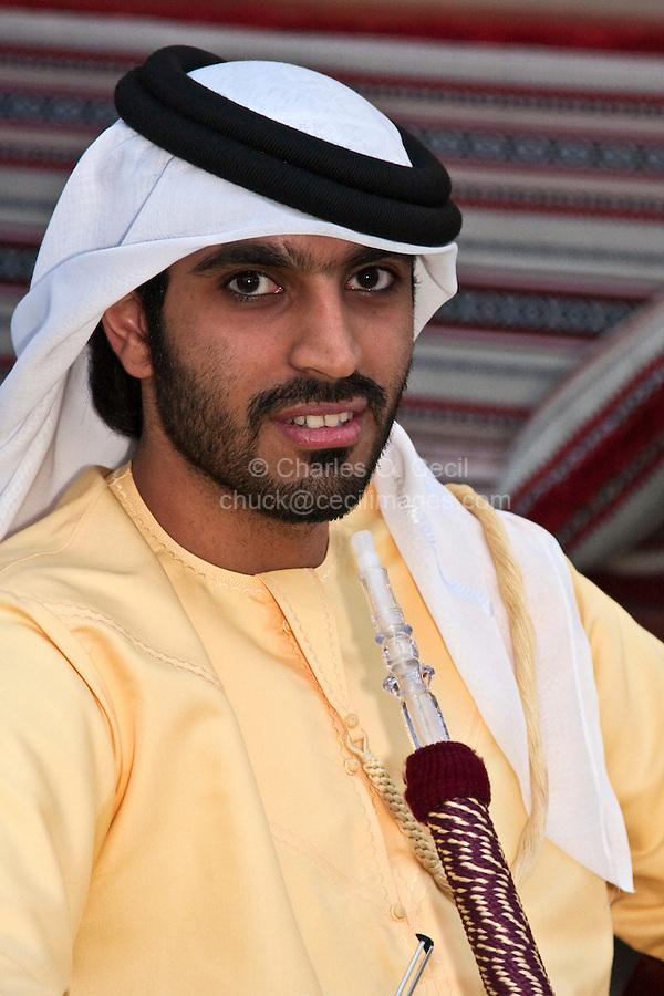 Doha, Qatar.  An Arab from Abu Dhabi Relaxing with a Water Pipe in a Coffee Shop in Doha.  He wears a yellow dishdasha, a white kaffiya (ghutra), and a black agal (egal), the traditional headdress of most Arabian Peninsula Arabs.