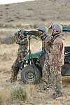 Helmet and camouflage wearing hunters use a spotting scope and binoculars to get a better look at a desert mule deer in New Mexico.