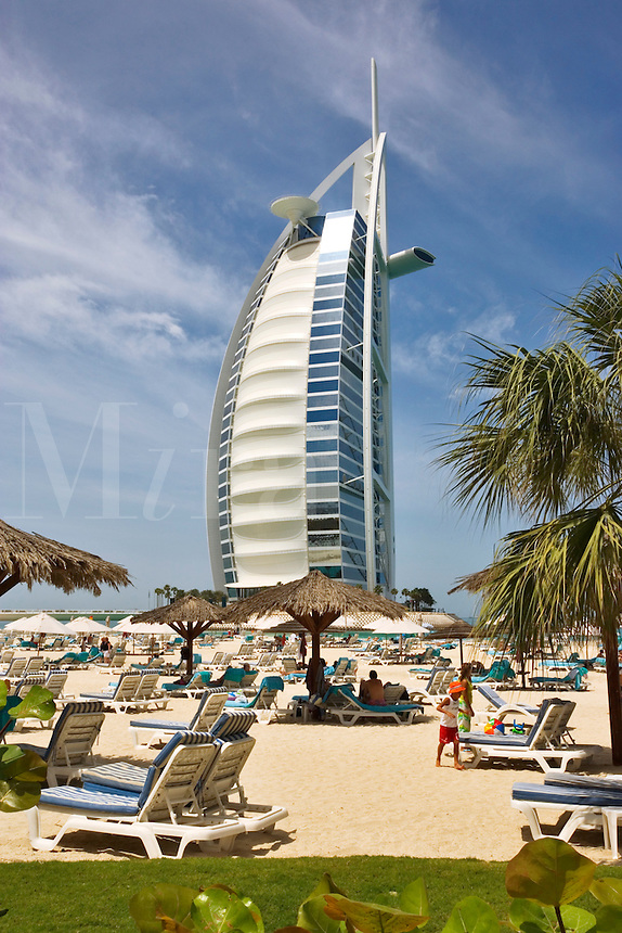 Burj al Arab Hotel, an icon of Dubai built in the shape of the sail of a dhow, stands on an artificial island just off Jumeirah Beach. View from beach at Jumeirah Beach Hotel.  Dubai. United Arab Emirates. Architects W.S. Atkins.