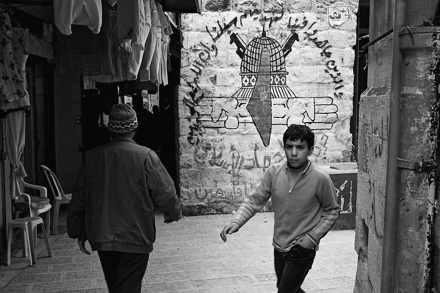 A young Palestinian boy and old Palestinain man walk by a mural in the old city of Nablus, the occupied West Bank, February 2006. Unemployment among young men in the old city has reached 80% according to the UNRWA. Photo: Ed Giles.