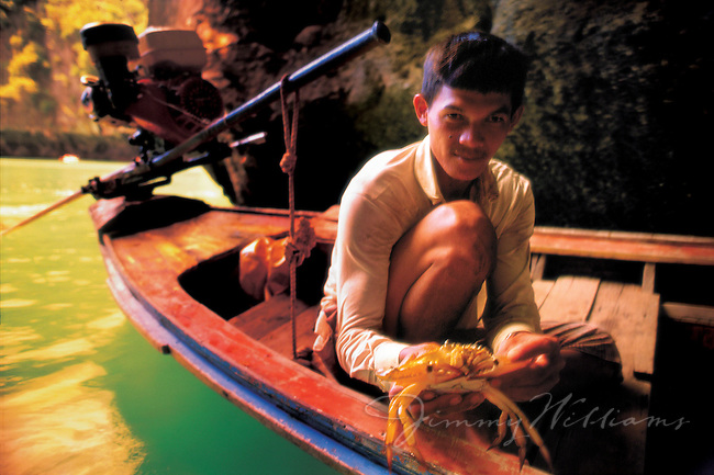 A fisherman shows off one of the crabs he just caught while fishing in Thailand.
