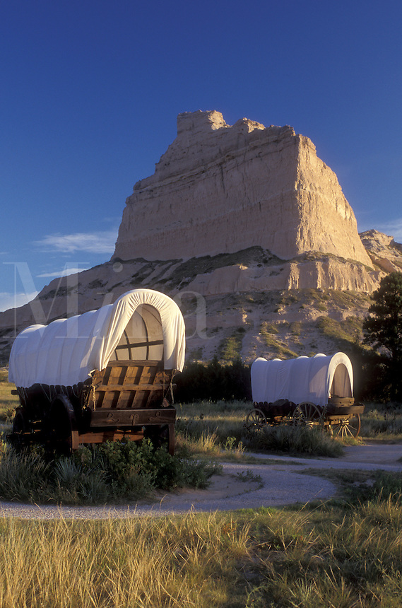 AJ0360, Scotts Bluff, Nebraska, Covered wagon exhibits with wind-sculpted bluff in background at Scotts Bluff National Monument.